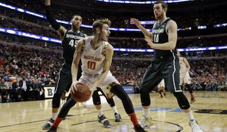 Maryland's Jake Layman (10) looks to pass under pressure from Michigan State's Denzel Valentine (45) and  Matt Costello (10) in the first half of an NCAA college basketball game in the semifinals of the Big Ten Conference tournament in Chicago, Saturday, March 14, 2015. (AP Photo/Nam Y. Huh)