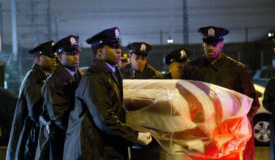 The remains of Philadelphia Police Officer Robert Wilson III are transferred to a horse drawn hearse during a winter rainstorm on Saturday, March 14, 2015, in Philadelphia. City officials said on March 5, 2015 Wilson was shot and killed after he and his partner exchanged gunfire with two suspects trying to rob a video game store.  (AP Photo/Matt Rourke)