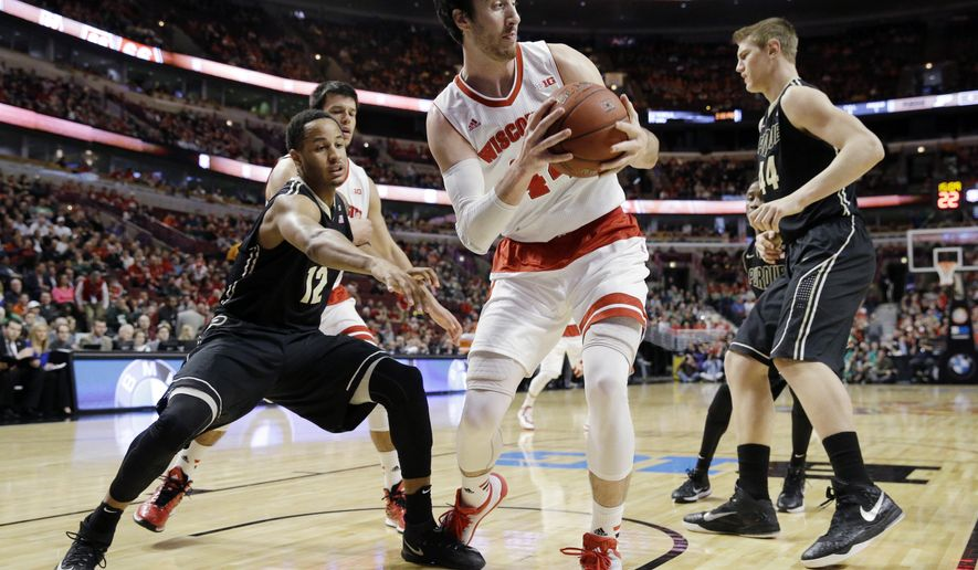 Wisconsin's Frank Kaminsky, center, grabs a rebound in front of Purdue's Vince Edwards (12) in the first half of an NCAA college basketball game in the semifinals of the Big Ten Conference tournament in Chicago, Saturday, March 14, 2015.  (AP Photo/Nam Y. Huh)