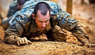 A soldier low crawls during basic combat training at Fort Benning, Ga., on March 9, 2012. (Image: Defense.gov)
