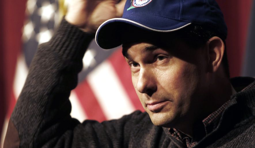 Wisconsin Gov. Scott Walker puts on a cap given to him by a member of the New Hampshire Gun Owners Association while answering questions at a training workshop for the New Hampshire state Republican Party in the auditorium at Concord High School Saturday, March 14, 2015, in Concord, N.H. (AP Photo/Jim Cole)