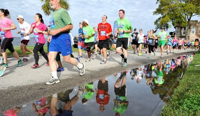 Runners reflect in water after just passing the 5k distance on River Road during the 38th Gate River Run 15k road race on Saturday March 14, 2015 in Jacksonville, Fla. (AP Photo/Florida Times-Union,Bruce Lipsky)