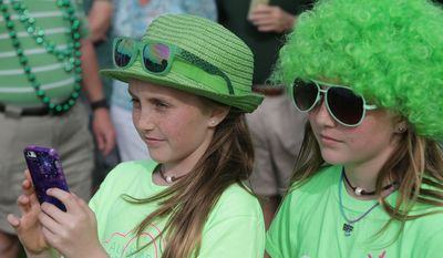 Twins Madison, left, and Alex Johnson, 11, watch the Panama City Pipes and Drums perform on Saturday, March 14, 2015, in St. Andrews, Fla. (AP Photos/Heather Leiphart, The News Herald)