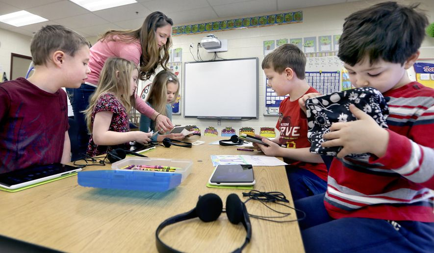 Bass-Hoover Elementary School teacher Jessica DeMarco, standing left, assists some of her students in readying their tablets for a reading assignment in Stephens City, Va., on Tuesday, March 10, 2015. (AP Photo/The Winchester Star, Ginger Perry)