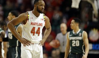 Maryland's Dez Wells (44) walks off the court in front of Michigan State's Travis Trice (20) for a time out  in the second half of an NCAA college basketball game in the semifinals of the Big Ten Conference tournament in Chicago, Saturday, March 14, 2015. Michigan State defeated Maryland 62-58. (AP Photo/Michael Conroy)