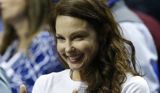 Actress Ashley Judd motions toward the Kentucky bench before the first half of the NCAA college basketball Southeastern Conference tournament championship game between Kentucky and Arkansas, Sunday, March 15, 2015, in Nashville, Tenn. (AP Photo/Steve Helber)