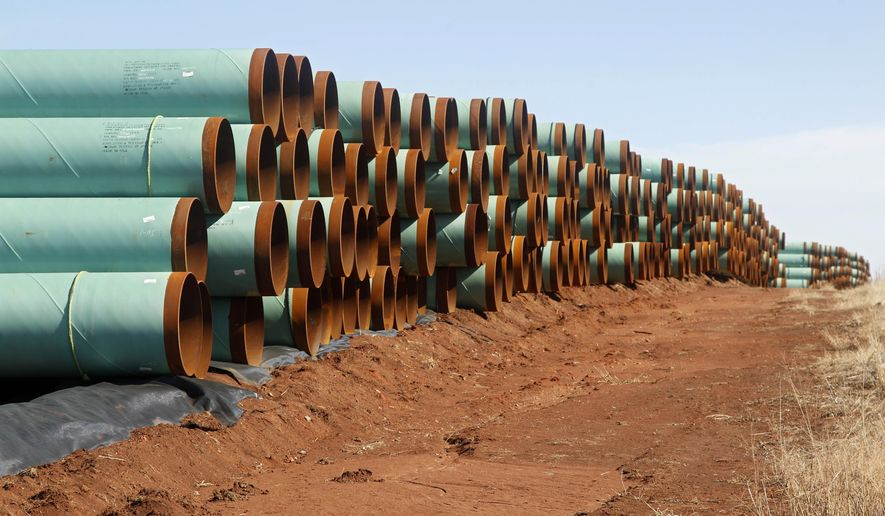 FILE - In this Feb. 1, 2012 file photo, miles of pipe for the stalled Canada-to-Texas Keystone XL pipeline are stacked in a field near Ripley, Okla. (AP Photo/Sue Ogrocki, File)