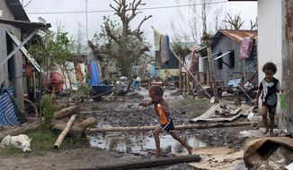 "In this March 15, 2015 photo provided by UNICEF Pacific, young children move around debris as residents work to recover from Cyclone Pam in Mele village, on the outskirts of the capital Port Vila, Vanuatu. Vanuatu's President Baldwin Lonsdale said the cyclone that hammered the tiny South Pacific archipelago was a ""monster"" that has destroyed or damaged 90 percent of the buildings in the capital and has forced the nation to start anew. (AP Photo/UNICEF Pacific) EDITORIAL USE ONLY, NO SALES"