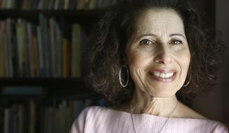 """In this Wednesday, March 11, 2015 photo, author Leslea Newman, of Holyoke, Mass., stands for a portrait at her home in Holyoke. Newman wrote the book """"Heather Has Two Mommies,"""" 25 years ago about a little girl named Heather and her two happy mommies that became a cultural and legal flashpoint. Newman has updated the book with fresh illustrations from a new artist. (AP Photo/Steven Senne)"""