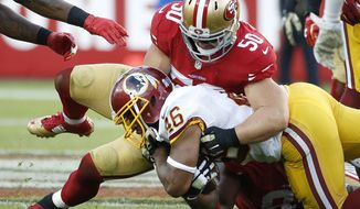 San Francisco 49ers inside linebacker Chris Borland (50) tackles Washington Redskins running back Alfred Morris (46) during the second half of an NFL football game in Santa Clara, Calif., Sunday, Nov. 23, 2014. (AP Photo/Tony Avelar)