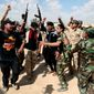 Iraqi fighters chant slogans against extremists at the front line during a battle against Islamic State militants in Tikrit, 130 kilometers (80 miles) north of Baghdad, Iraq, Monday, March 16, 2015. The offensive to retake Saddam Hussein's hometown of Tikrit began March 2. The city is one of the largest held by the Islamic State militants on the road connected Baghdad and Mosul. (AP Photo/Khalid Mohammed)