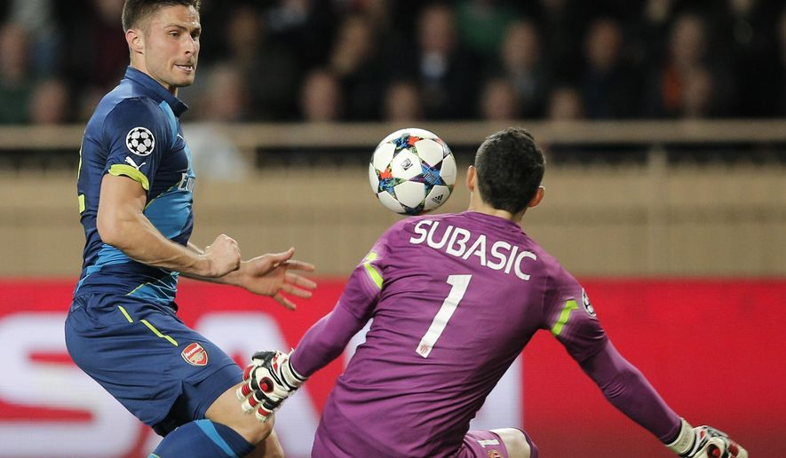 Arsenal's Olivier Giroud, left, faces Monaco's goalkeeper Danijel Subasic  during their Champions League round of 16 second leg soccer match between Monaco and Arsenal at Louis II stadium in Monaco, Tuesday, March 17, 2015. (AP Photo/Christophe Ena)