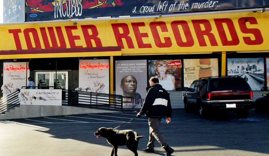 """FILE - In this Feb. 9, 2004 file photo, a pedestrian walks through the parking lot of Tower Records in Los Angeles. """"All Things Must Pass,"""" a documentary by Colin Hanks about Tower Records, the retail store that dominated for decades before filing for bankruptcy in 2006, earned at standing ovation at the South by Southwest festival on Tuesday, March 17, 2015. (AP Photo/Ric Francis, File)"""