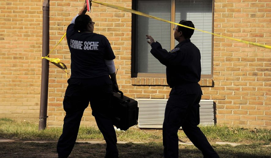 Crime scene investigators step beneath police tape to document the scene and gather evidence where a stabbing took place at Morgan State University, Tuesday, March 17, 2015, in Baltimore. Two groups of people got into a fight outside a dining hall on the Morgan State University campus, and some football players were stabbed by someone swinging a knife wildly, police and college officials said. (AP Photo/The Baltimore Sun, Karl Merton Ferron)