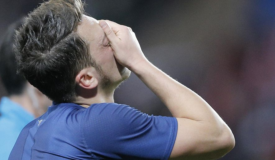 Arsenal's Mesut Ozil reacts after their Champions League round of 16 second leg soccer match between Monaco and Arsenal at Louis II stadium in Monaco, Tuesday, March 17, 2015. Monaco advances in Champions League on away goals rule after 2-0 loss . (AP Photo/Christophe Ena)
