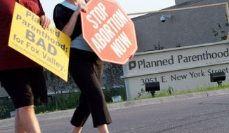 Protesters march near a Planned Parenthood location in Aurora, Ill., on Sept. 18, 2007. Some Illinois lawmakers are seeking to require annual inspections for all the state's abortion clinics, more than three years after officials took steps to reinforce the system following a report by The Associated Press that some facilities had gone 15 years without an inspection. (Associated Press) **FILE**