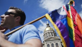 "The dome of the Capitol stands in the background as Stephen Saras, of Atlanta, holds a rainbow colored flag during a rally against a contentious ""religious freedom"" bill, Tuesday, March 17, 2015, in Atlanta. The Georgia Senate gave decisive approval to the bill, one of a wave of measures surfacing in at least a dozen states that critics say could provide legal cover for discrimination against gays and transgender people. (AP Photo/David Goldman)"