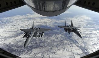 Two F-15E Strike Eagles wait to receive fuel from a KC-135R Stratotanker Jan. 23, 2015, on their way to Nellis Air Force Base, Nev., in support of Red Flag 15-1. (U.S. Air Force photo by Airman 1st Class Aaron J. Jenne/Released) ** FILE **