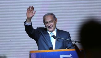 Israeli Prime Minister Benjamin Netanyahu greets supporters at the party's election headquarters In Tel Aviv. Wednesday, March 18, 2015. (AP Photo/Oded Balilty)