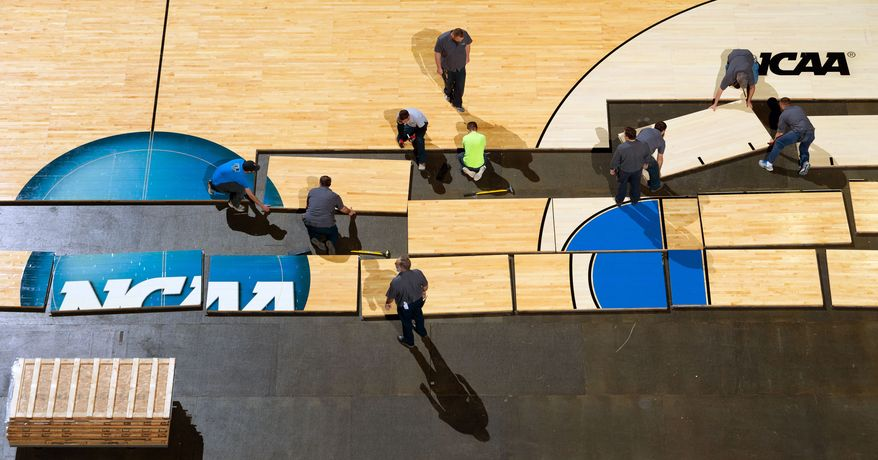 Workers place the basketball court on the floor at the CenturyLink Center in Omaha, Neb., Tuesday March 17, 2015. The second and third rounds of the NCAA Men's Basketball Tournament will take place this weekend. (AP Photo/Omaha World-Herald/Matt Miller) mags out tv out  (AP Photo/The World-Herald, ) MAGS OUT; ALL NEBRASKA LOCAL BROADCAST TELEVISION OUT