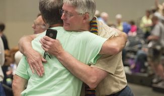 """FILE - In this June 19, 2014, file photo, Gary Lyon, left, of Leechburg, Pa., and Bill Samford, of Hawley, Pa., celebrate after a vote allowing Presbyterian pastors discretion in marrying same-sex couples at the 221st General Assembly of the Presbyterian Church at Cobo Hall, in Detroit. The Presbyterian Church (U.S.A.) approved redefining marriage in the church constitution Tuesday, March 17, 2015, to include a """"commitment between two people,"""" becoming the largest Protestant group to formally recognize gay marriage as Christian and allow same-sex weddings in every congregation. (AP Photo/Detroit News, David Guralnick, File)"""