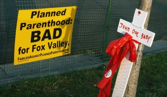 Signs and crosses are seen near a Planned Parenthood location in Aurora, Ill., on Sept. 18, 2007. Some Illinois lawmakers are seeking to require annual inspections for all the state's abortion clinics, more than three years after officials took steps to reinforce the system following a report by The Associated Press that some facilities had gone 15 years without an inspection. (AP Photo/Stacie Freudenberg, File)