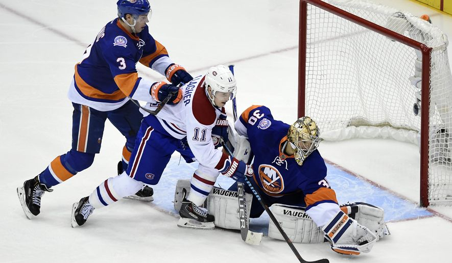 New York Islanders goalie Michal Neuvirth (30) stops a shot on goal by Montreal Canadiens right wing Brendan Gallagher (11) as Islanders defenseman Travis Hamonic (3) defends in the third period of an NHL hockey game on Saturday, March 14, 2015, in Uniondale, N.Y. The Canadiens won 3-1. (AP Photo/Kathy Kmonicek)