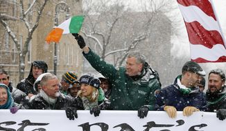 FILE - In this March 1, 2015 file photo, New York Mayor Bill de Blasio, waves the flag of Ireland as he marches beside Kerry Kennedy, third from left, during the all-inclusive St. Pat's For All parade in the Sunnyside, Queens neighborhood of New York. The parade, which embraces diversity and inclusion, is considered an alternative to the New York City's official St. Patrick's Day parade on March 17. (AP Photo/Kathy Willens, File)