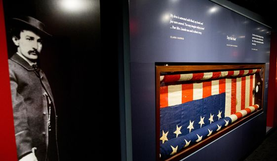 "A large photograph depicting President Abraham Lincoln's assassin John Wilkes Booth is displayed next to the bunting flag hung from the presidential box at the historic Ford's Theatre at a new exhibit entitled ""Silent Witnesses: Artifacts of the Lincoln Assassination"" Tuesday, March 17, 2015, at the Ford's Center for Education and Leadership in Washington. (AP Photo/Andrew Harnik) ** FILE **"