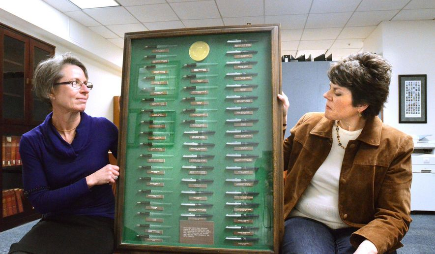 Dominique Daniel, Oakland University coordinator of university archives, left, and Shirley Paquette, archives assistant hold a display in Auburn Hills, Mich., March 10, 2015, of 50 pens used by President Lyndon Johnson to sign legislation in 1965. The pens where donated to the university by Billy Farnum, a one term U. S. Congressman.   (AP Photo/The Oakland Press, Tim Thompson)