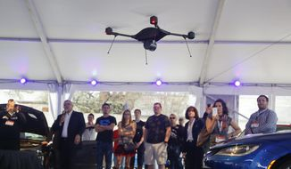 "In this March 14, 2015, file photo, a crowd observes an Indago drone demonstration during the ""Tech Chat: How Drones Can Aid Transportation"" at the C3 Group's Connected Car Pavilion during the SXSW Interactive Festival in Austin, Texas. The Indago can be equipped with a thermal camera, has a 45-minute capacity battery, auto-pilot features, a range over 5 line-of-sight miles, and can carry a payload of up to one pound. (AP Photo/Jack Plunkett, File)"