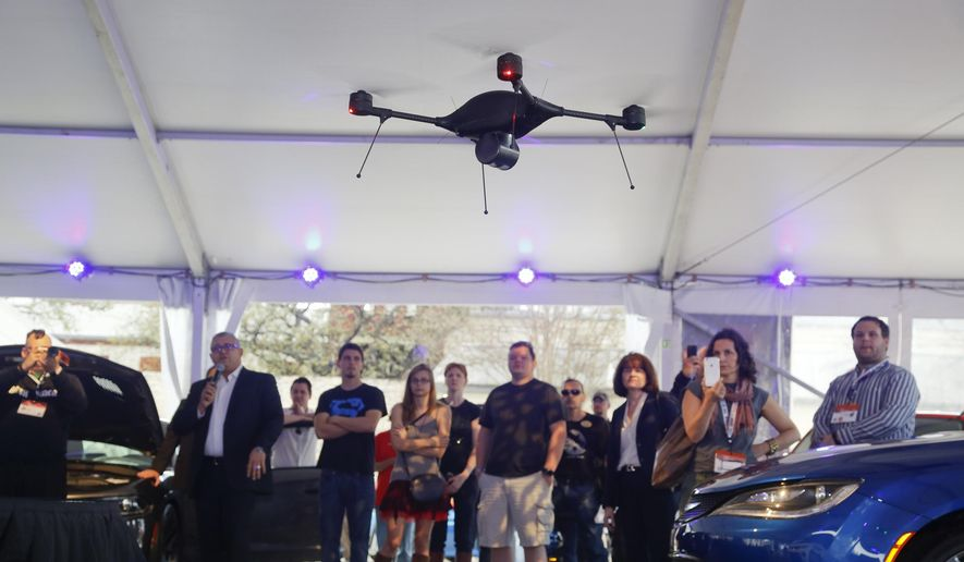 """In this March 14, 2015, file photo, a crowd observes an Indago drone demonstration during the """"Tech Chat: How Drones Can Aid Transportation"""" at the C3 Group's Connected Car Pavilion during the SXSW Interactive Festival in Austin, Texas. The Indago can be equipped with a thermal camera, has a 45-minute capacity battery, auto-pilot features, a range over 5 line-of-sight miles, and can carry a payload of up to one pound. (AP Photo/Jack Plunkett, File)"""