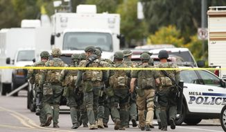 A SWAT team walks down the street near Adams Elementary School searching for a gunman on Wednesday, March 18, 2015 in Mesa, Ariz. A gunman wounded at least four people across multiple locations in the Phoenix suburb. The first shooting happened at a motel, and people were also wounded at a restaurant and nearby apartment complexes.  (AP Photo/The Arizona Republic, Rob Schumacher)  MARICOPA COUNTY OUT; MAGS OUT; NO SALES