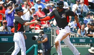 Miami Marlins' Giancarlo Stanton is congratulated by third base coach Brett Butler (2) as he rounds third base after hitting a solo home run in the sixth inning of an exhibition spring training baseball game against the Washington Nationals, Wednesday, March 18, 2015, in Jupiter, Fla.  (AP Photo/John Bazemore)