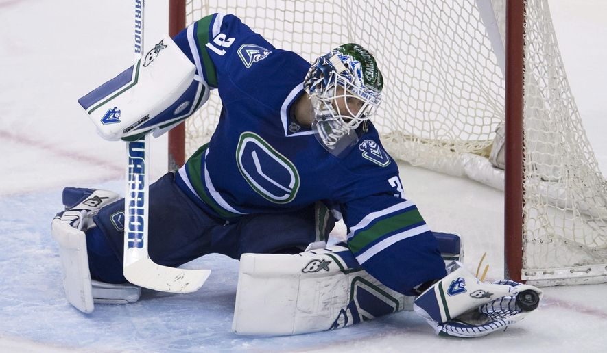 Vancouver Canucks goalie Eddie Lack (31) makes a save during the third period of NHL action against the Philadelphia Flyers in Vancouver, Canada Tuesday, March. 17, 2015. (AP Photo/The Canadian Press, Jonathan Hayward)