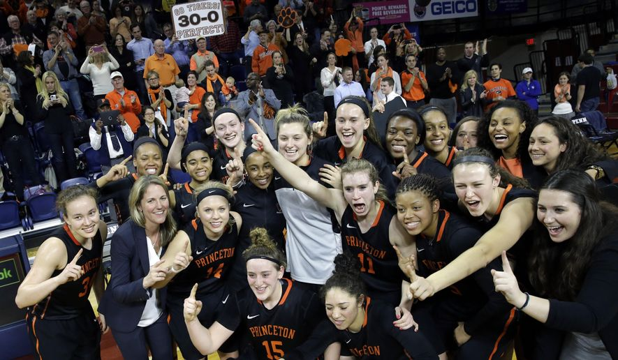 FILE - In this Tuesday, March 10, 2015 file photo, a fan holds a sign as the Princeton players pose for photographs after defeating Pennsylvania in an NCAA college basketball game Tuesday, March 10, 2015, in Philadelphia, Pa. Princeton won 55-42 to end a perfect season. Not everyone is all that enamored with Princeton's perfect season, most notably the women's NCAA Tournament selection committee.The committee made the Tigers an eight seed heading into the tournament which begins Friday, March 20, 2015.(AP Photo/Mel Evans, FIle)