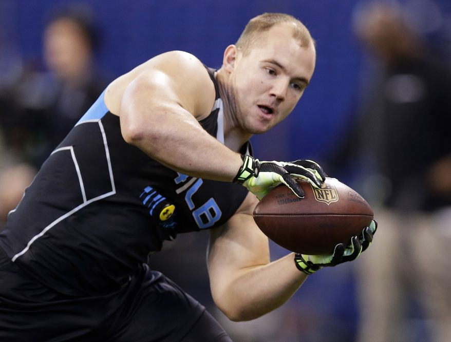 FILE - In this Feb. 24, 2014 file photo, Wisconsin linebacker Chris Borland makes a catch as he runs a drill at the NFL football scouting combine in Indianapolis. Borland is one of the most heralded linebackers to come out of Wisconsin, but questions remain about how his skills might carry over to the NFL. (AP Photo/Michael Conroy, File)