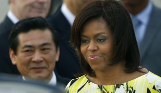 U.S. first lady Michelle Obama smiles upon her arrival at Haneda International Airport in Tokyo Wednesday, March 18, 2015. Obama is visiting Japan and Cambodia, who are among Asia's richest and poorest nations, to highlight cooperation on helping girls finish their educations. (AP Photo/Shizuo Kambayashi)