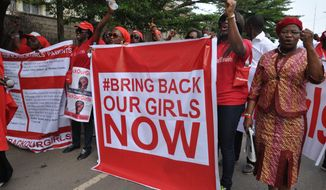 FILE - In this Tuesday Oct. 14, 2014 file photo, people demonstrate calling on the Nigerian government to rescue girls taken from a secondary school in Chibok region, in the city of Abuja, Nigeria. Nigeria's military says it has no news of the more than 200 schoolgirls kidnapped by Islamic extremists nearly a year ago, despite liberating dozens of towns from the girls' Boko Haram abductors. (AP Photo/Olamikan Gbemiga, File)