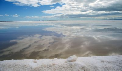 In this March 3, 2015 photo, a cloudy blue sky is reflected in a flood zone used to evaporate sea salt by salt producer Salt Export Co. (ESSA), in Guerrero Negro, Mexico's Baja California peninsula. Salt is made by drawing sea water into ponds and then allowing wind and sunshine to evaporate the excess water. (AP Photo/Dario Lopez-Mills)