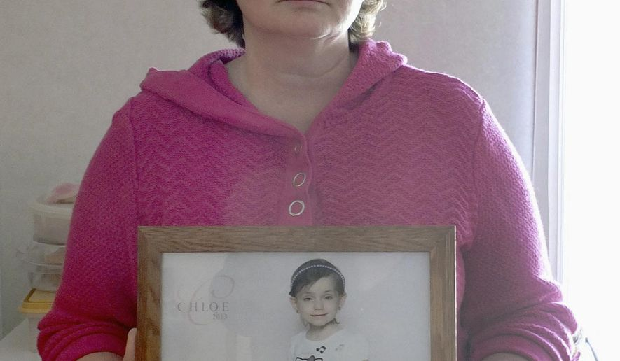 In this Feb. 15, 2015 photo, Jeanie West, who lives near Cowden, Ill., holds a photo of her granddaughter Chloe West who passed away in 2013 from leukemia at age 5. West is holding her second toy collection for St. Louis Children's Hospital in her granddaughter's honor. (AP Photo/Effingham Daily News, Stan Polanski)