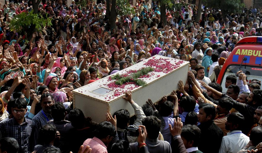 Pakistani Christians carry a casket of a victim of Sunday's pair of suicide attacks on two churches during a mass funeral service in Lahore, Pakistan, Tuesday, March 17, 2015. Pakistan's minority Christians buried the victims of Sunday's suicidein the eastern city of Lahore amid tight security. (AP Photo/K.M. Chaudary)
