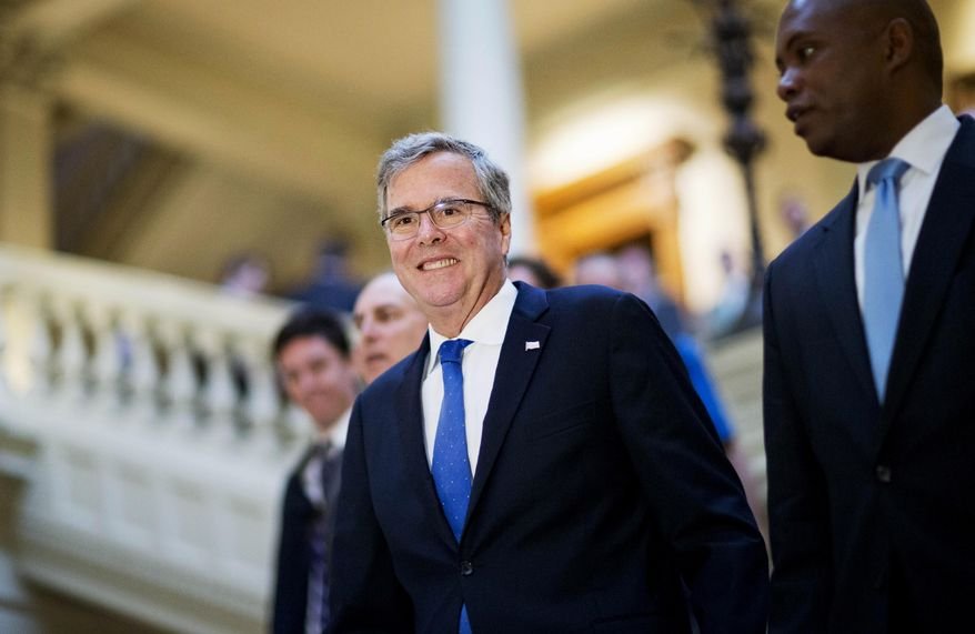Former Florida Gov. Jeb Bush walks with former campaign staff member Rufus Montgomery, right, while visiting the Georgia Capitol, Thursday, March 19, 2015, in Atlanta. (AP Photo/David Goldman)