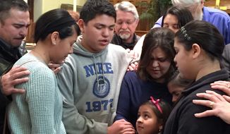 Gloria Villatoro joins her children and community members in prayer at the Trinity United Methodist Church in Des Moines, Iowa. Max Villatoro was arrested by immigration officials and faces deportation under new administration rules. (Associated Press)