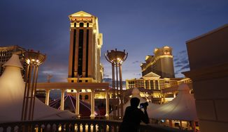 In this Monday, Jan. 12, 2015, file photo, a man takes pictures of Caesars Palace hotel and casino, in Las Vegas. (AP Photo/John Locher, File)