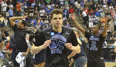 Georgia State's R.J. Hunter (22) comes off the court after making a game winning shot against Baylor, as head coach Ron Hunter, back left, and Ryann Green (2) celebrate their 57-56 in the second round of the NCAA college basketball tournament, Thursday, March 19, 2015, in Jacksonville, Fla. (AP Photo/Rick Wilson)