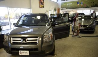 Buyers look over a 2008 Pilot sports-utility vehicle while a 2008 Accord coupe sits in the background at a Honda dealership in the south Denver suburb of Littleton, Colo., in this Oct. 18, 2007, file photo. Honda is adding nearly 105,000 vehicles to its U.S. recall of driver's side air bag inflators that can explode with too much force. (AP Photo/David Zalubowski, FILE)
