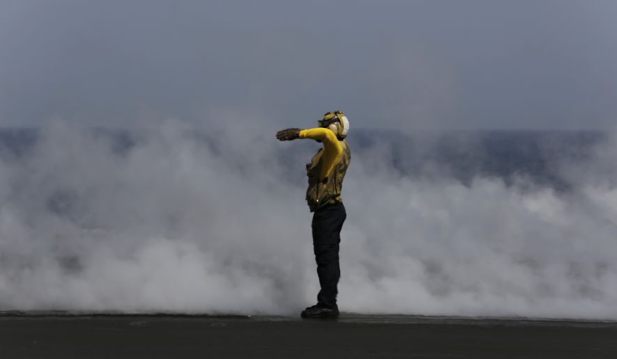 A U.S. sailor guides a military jet preparing for takeoff just after another has catapulted off the deck of the USS Carl Vinson aircraft carrier in the Persian Gulf, Thursday, March 19, 2015. U.S. aircraft aboard the Carl Vinson as well as French military jets aboard the nearby French carrier Charles de Gaulle are flying missions over Iraq in the fight against Islamic State militants. (AP Photo/Hasan Jamali)