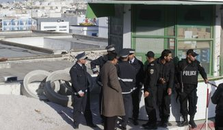 Tunisian police officers  gather at the entrance of the morgue of the Charles Nicolle hospital in Tunis Tunisia, Thursday, March 19, 2015. The radical Islamic State Group claimed responsibility Thursday for the attack on a famed Tunis museum that left 23 people dead. (AP Photo / Michel Euler)