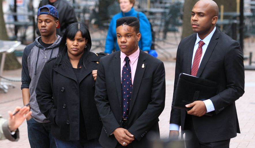 Lawyer Daniel Watkins, right, stands with UVa student Martese Johnson, center, his mother Dychea and his brother Michael, left, before making a statement at a press conference Thursday, March 19, 2015, on the Downtown Mall in Charlottesville, Va. Johnson was bloodied during an arrest March 18, 2015 about 1 a.m. by State Alcoholic Beverage Control agents outside Trinity Irish Pub on the Corner near the University of Virginia. (AP Photo/The Daily Progress, Andrew Shurtleff)